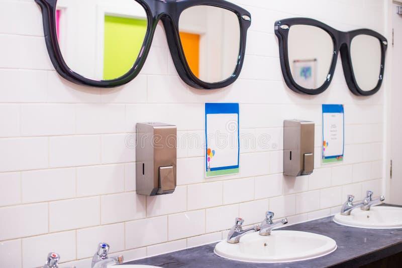 Fregadero del lavado y espejos grandes en la forma de los vidrios en el retrete público, fila del lavabo inglés de dos grúas en l foto de archivo libre de regalías