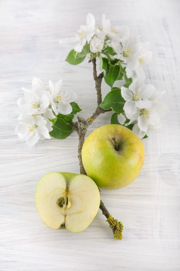 Freh rijpe groene die appel met mooie appelbloesem wordt verfraaid op witte houten lijst royalty-vrije stock foto