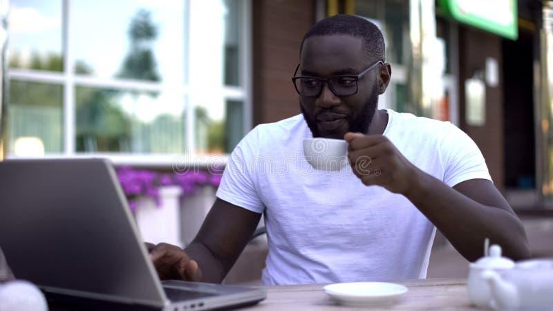 Freiberufler, der im Café und in trinkendem Tee, Fernarbeit, Job für Studenten arbeitet stockfotos