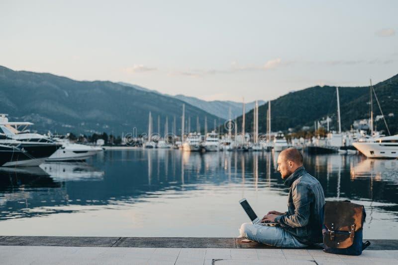 Freiberufler, der an Laptop auf dem Ufer nahe dem Yachtboot an arbeitet lizenzfreies stockfoto