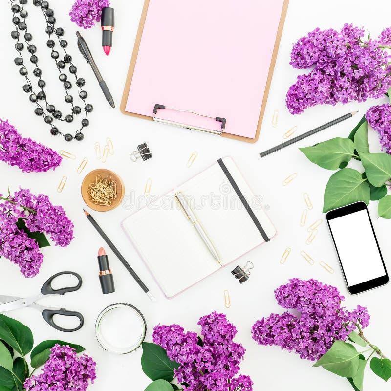 Freiberufler- oder Bloggerarbeitsplatz mit Klemmbrett, Handy, Notizbuch, Kosmetik, lila Blumen und Zubehör auf weißem backgrou stockbild