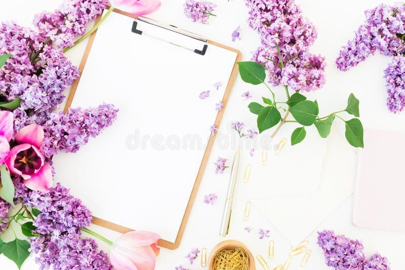 Freiberufler- oder Bloggerarbeitsplatz mit Klemmbrett, Notizbuch, Umschlag, Flieder und Tulpen auf weißem Hintergrund Flache Lage lizenzfreie stockbilder