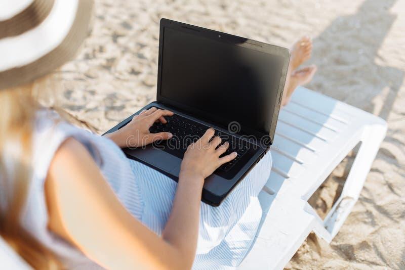 Freiberuflermädchen, das im Urlaub, vor dem schönen Meer, sitzend mit einem Laptop auf dem Ozean arbeitet stockbilder