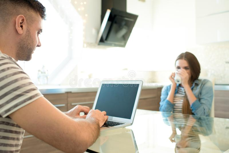 Freiberuflich tätiger Ehemann, der mit Laptop arbeitet lizenzfreie stockbilder