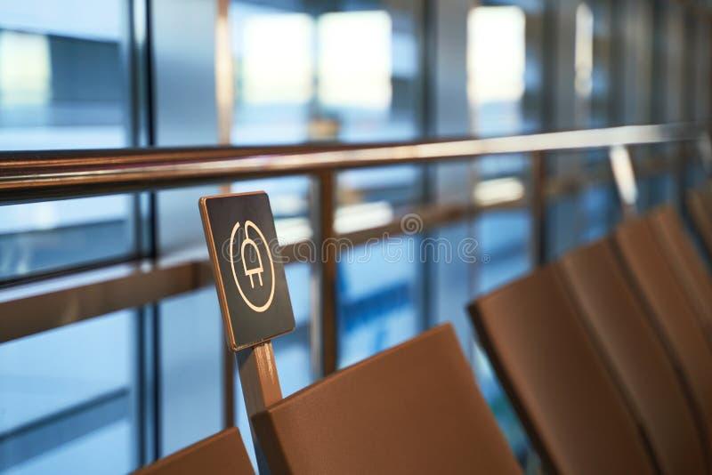 Freie Batterieladestation nahe Sitzen im internationalen Flughafen für Reisende lizenzfreies stockbild