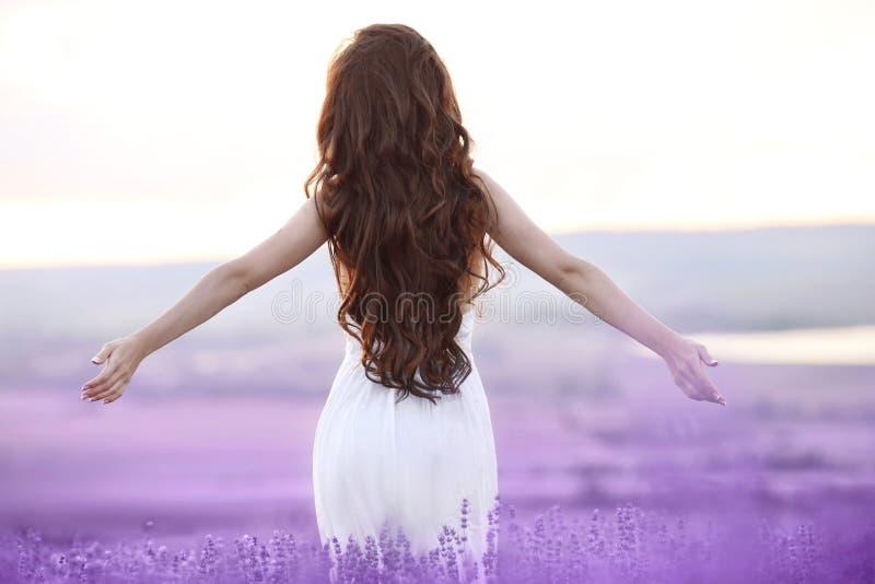 Freie Brunettefrau mit den offenen Armen Sonnenuntergang in Lavendel f genießend lizenzfreie stockfotografie