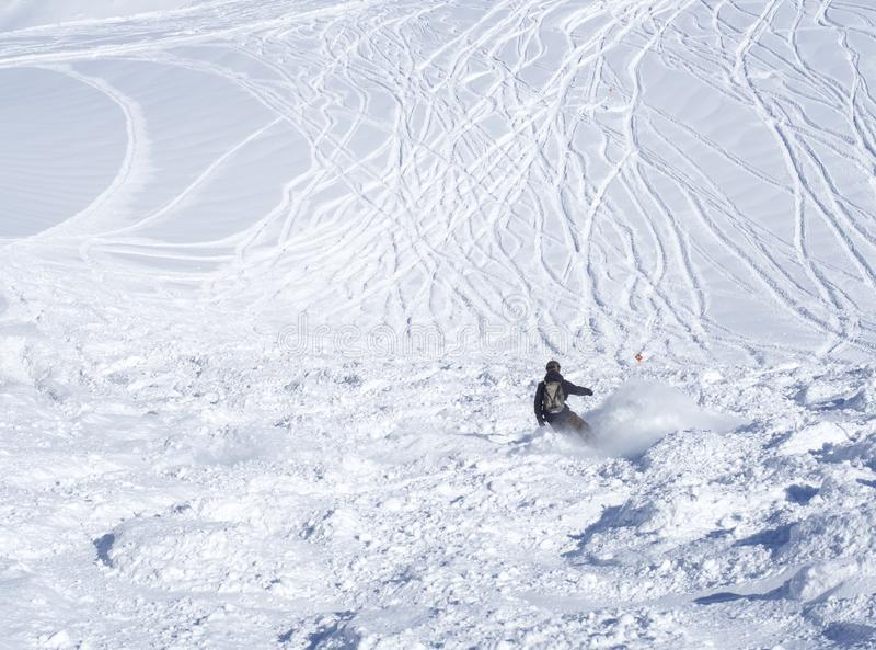 Freie Fahrtpiste mit dem freerider Snowboarder, der abwärts auf Schnee Ski fährt, umfasste Steigungen von der Spitze Kitzsteinhor stockbild