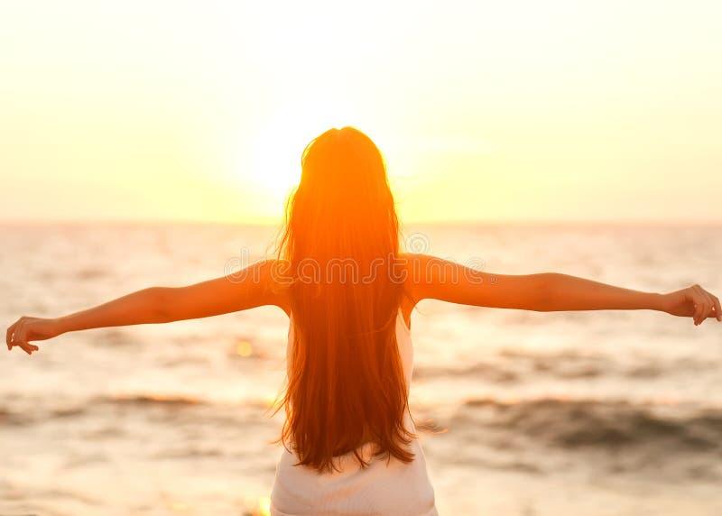 Freie Frau, welche die Freiheit sich fühlt glücklich am Strand bei Sonnenuntergang genießt Seien Sie lizenzfreie stockfotografie