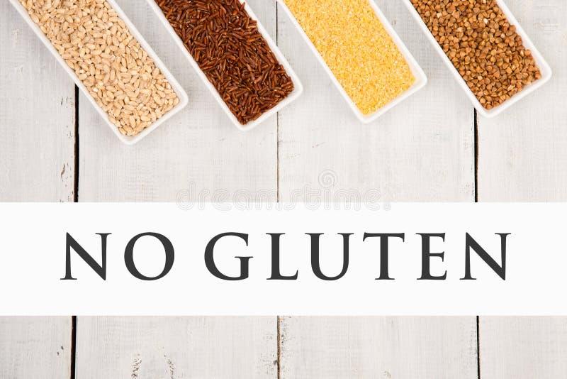 Freie Getreide des Glutens in den Schüsseln - Maiskörner, brauner Buchweizen, roter Reis, Perlgerste mit Text kein Gluten stockfoto