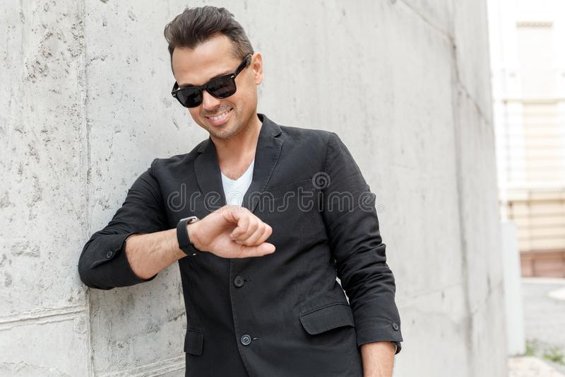 Freienfreizeit Junger Mann in der Klage und Sonnenbrille auf der Stadtstraße lokalisiert auf Wand lächelnden aufgeregten Abschlus lizenzfreie stockfotografie