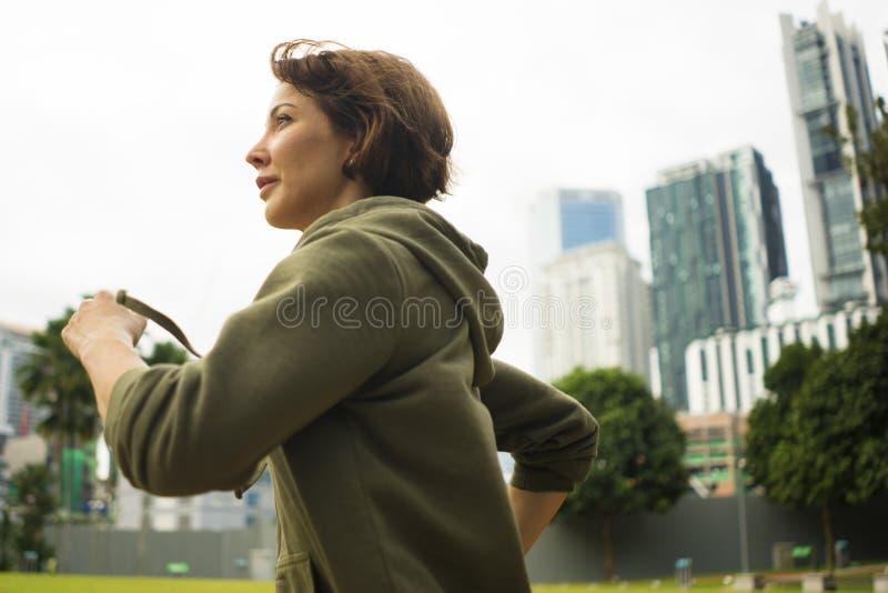Freienporträt der jungen attraktiven und aktiven Rüttlerfrau im Hoodiespitzenbetrieb und -c$rütteln in der Morgengymnastik an sch lizenzfreie stockfotos