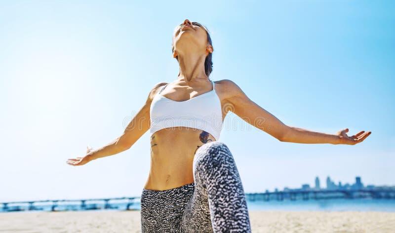 Freienporträt der jungen dünnen athletischen Frauenstellung in Yoga asana mit den angehobenen Armen auf der Stadt und dem blauen  lizenzfreie stockbilder