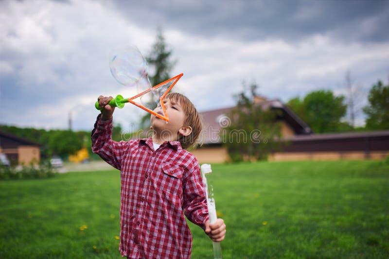 Freienportr?t von Schlagseifenblasen des netten Vorschuljungen auf einem gr?nen Rasen am Spielplatz lizenzfreie stockfotos