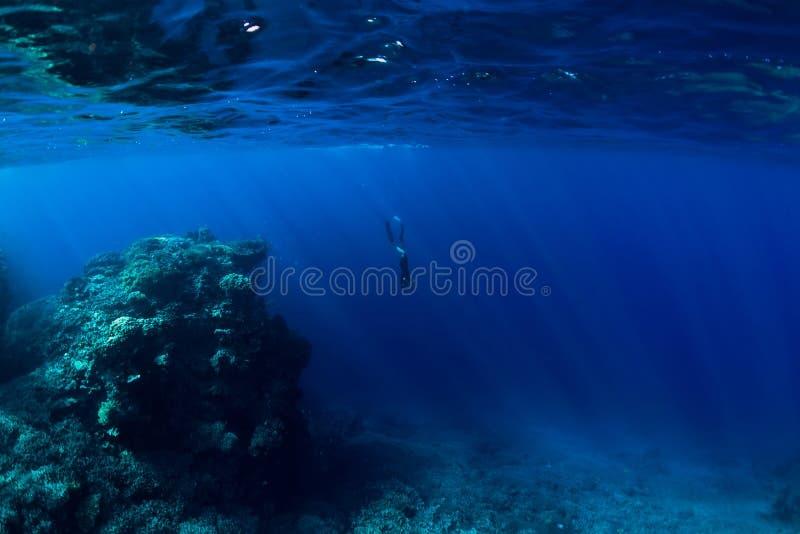 Freier Taucher Unterwasser im Ozean mit Felsen und Koralle stockfotos