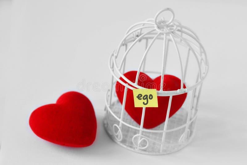 Freies Herz und Herz in einem Vogelkäfig mit dem Wort Ego an geschrieben lizenzfreies stockbild