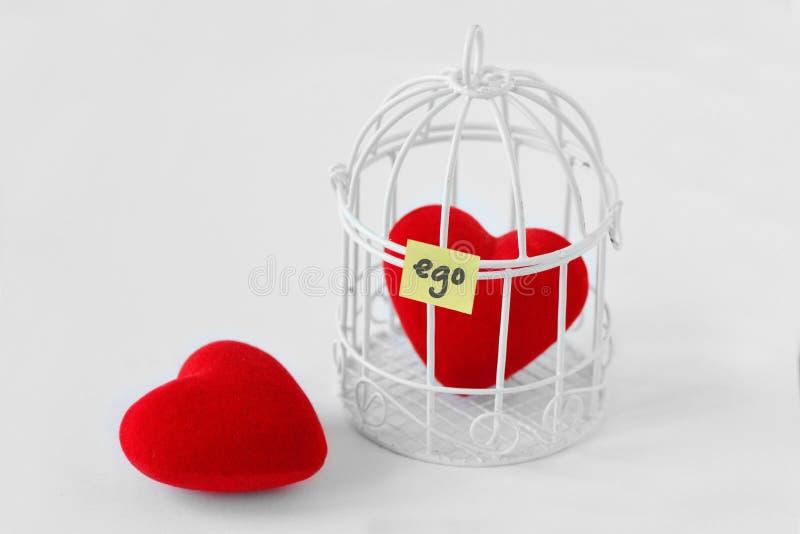 Freies Herz und Herz in einem Vogelkäfig mit dem Wort Ego an geschrieben stockfoto