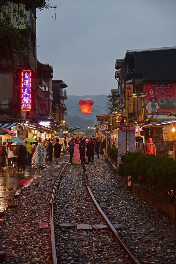 Freigeben der Laterne in den Himmel beim Halten von umbreall an einem regnerischen Tag an alten Straßen Shifen Ende des Abends lizenzfreies stockfoto