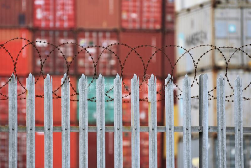 Freight Containers behind a fence topped with barbed wire at the port of Southampton, UK. Jan 2019. Stacked freight shipping containers behind a security fence stock photo