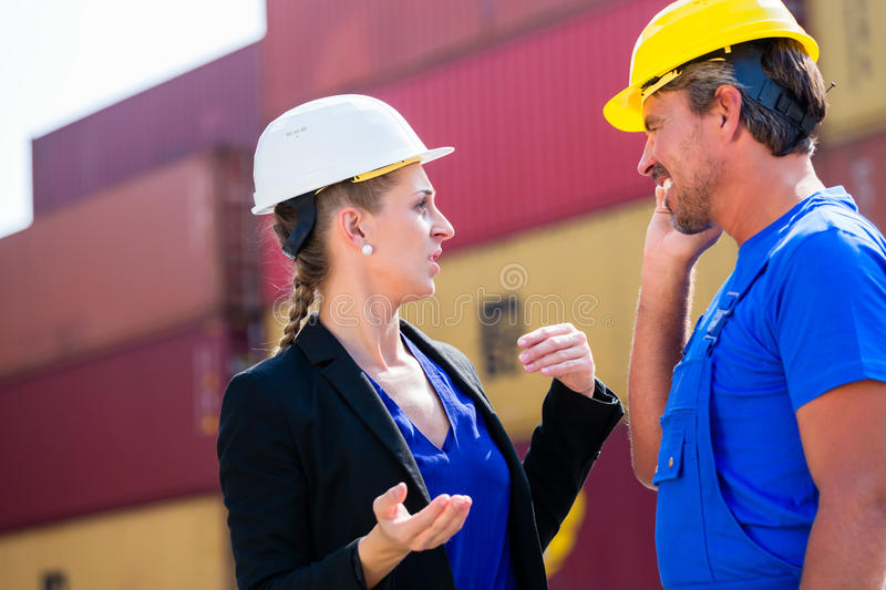 Freight shipping at container terminal of port. Worker and manager discussing shipments stock images