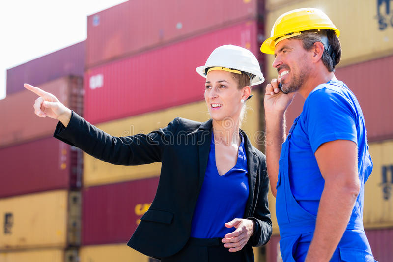 Freight shipping at container terminal of port. Worker and manager discussing shipments stock photography