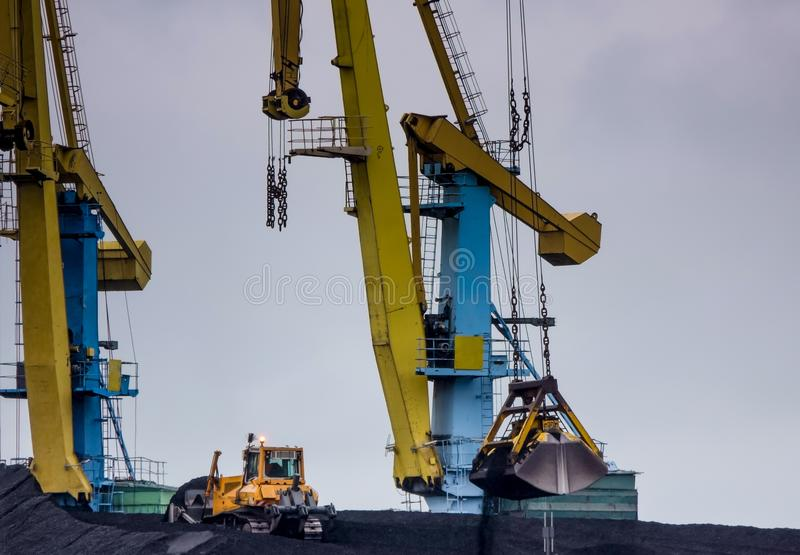 In freight terminal, gantry crane and cargo ships are in loading and unloading of goods stock photos
