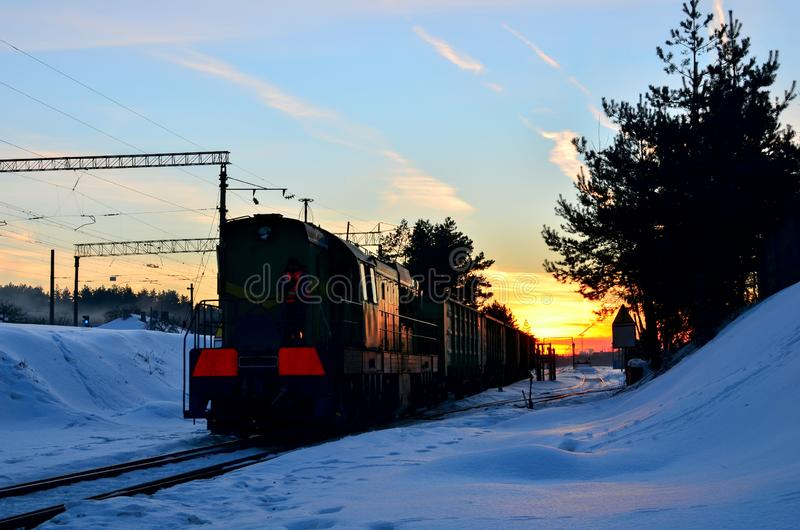 Freight train with cars on the railway leaves the depot against the backdrop of an incredible sunset in the winter period. royalty free stock photos