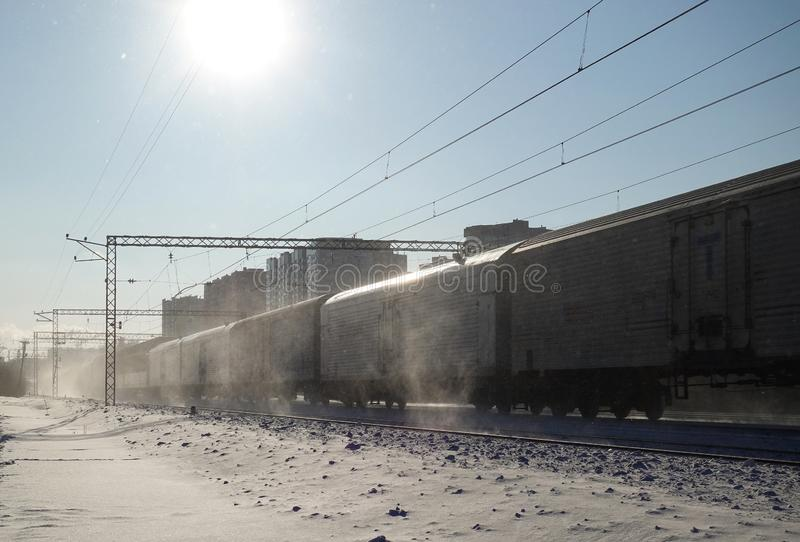 Freight train moves at high speed in winter after heavy snowfall. Partially slight motion blur. Russia stock photography