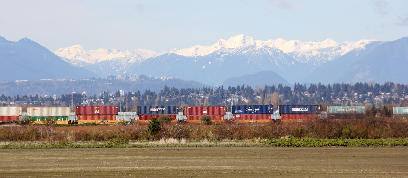 Freight Train passing Scenic Mountain backdrop to Vancouver, BC royalty free stock photo