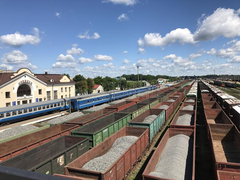 Freight trains at the railway station. Open freight wagons with cargo. And railway tanks stock photography