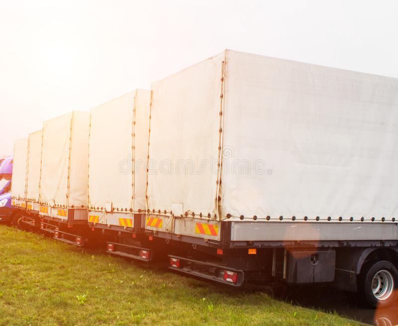 Freight vans stand in a row, rear view, trucking industry and sun. Trucking royalty free stock photo
