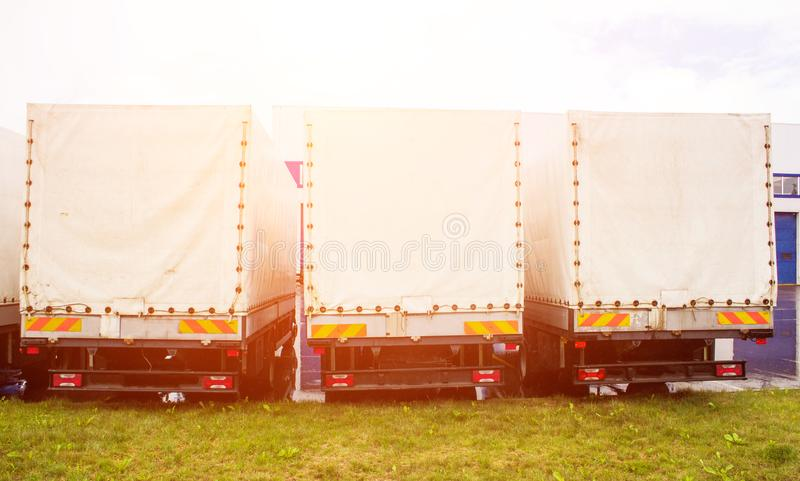 Freight vans stand in a row, rear view, trucking industry and sun, trucking. Trailer royalty free stock image