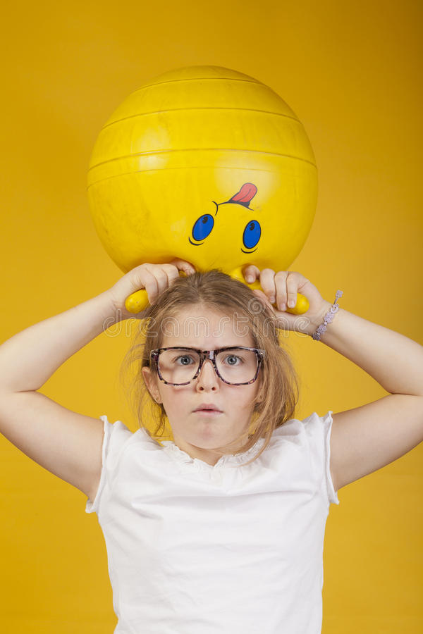Freighten Look Of A Young Girl With A Yellow Ball Royalty Free Stock Photo