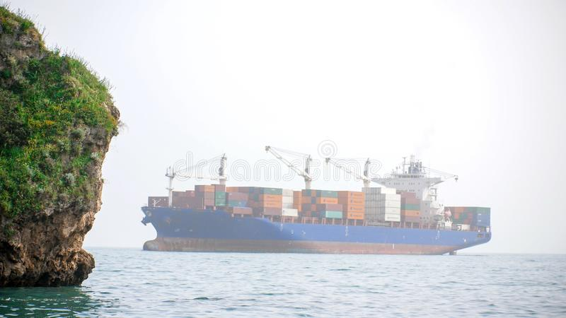 Freighter with multiple containers floats in the sea. Shot from afar stock image