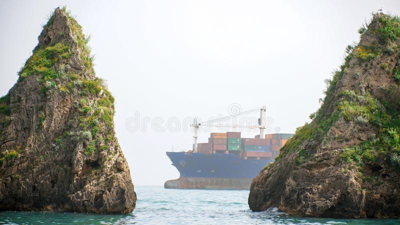 Freighter with multiple containers floats in the sea between the two reefs. Shot from afar stock image