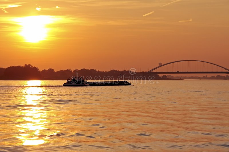 Freighter on river Merwede in the Netherlands. At sunset royalty free stock images