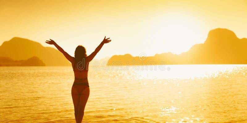Freiheits- und Gl?ckfrau auf Strand Sie genie?t ruhige Ozeannatur w?hrend der Reise, die Feiertage drau?en Urlaub machen lizenzfreie stockfotografie