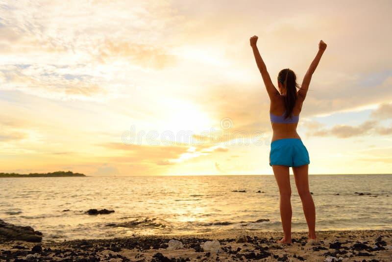 Freiheitserfolgsfrau, die am Sonnenuntergangstrand zujubelt stockbilder