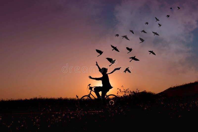 Freiheitskonzept, Schattenbild des glücklichen Menschen hob Arme auf bicyc an lizenzfreie stockfotos