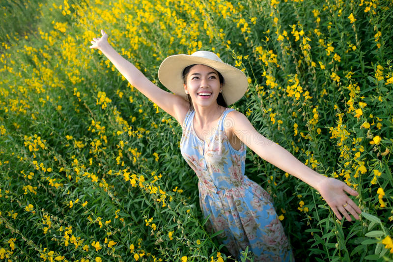 Freiheitsmädchen, das mit Blumen auf Feld genießt, stockfotografie