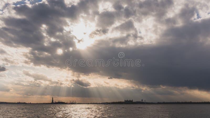 Freiheitsstatue ?ber Wasser bei Sonnenuntergang, in New York City, USA lizenzfreie stockbilder