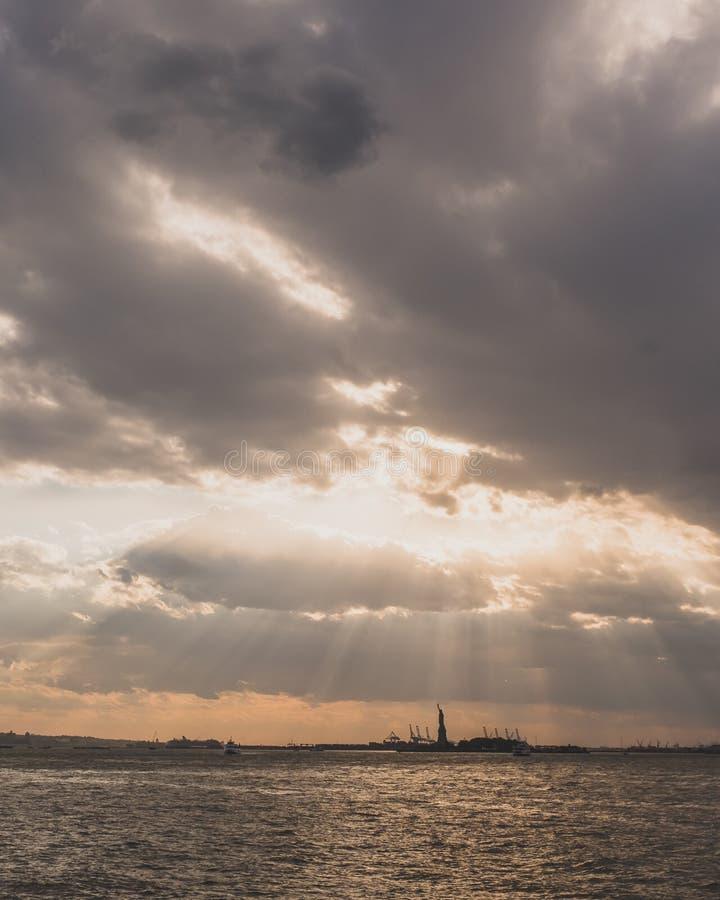 Freiheitsstatue ?ber Wasser bei Sonnenuntergang, in New York City, USA lizenzfreies stockfoto