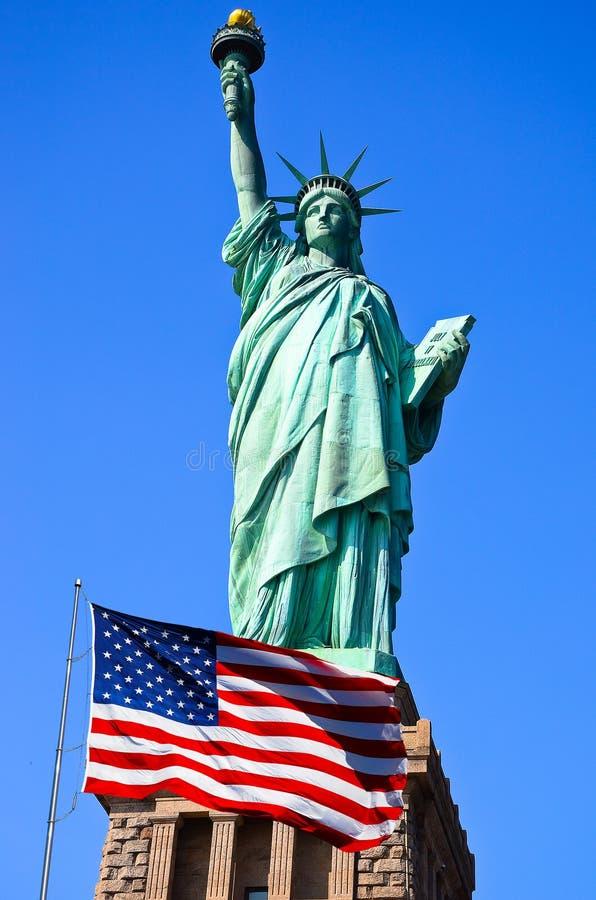 Freiheitsstatue und Vereinigter Staaten Flagge in New York City stockbilder