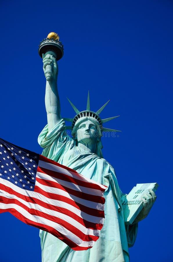 Freiheitsstatue und Vereinigter Staaten Flagge in New York City lizenzfreie stockfotografie