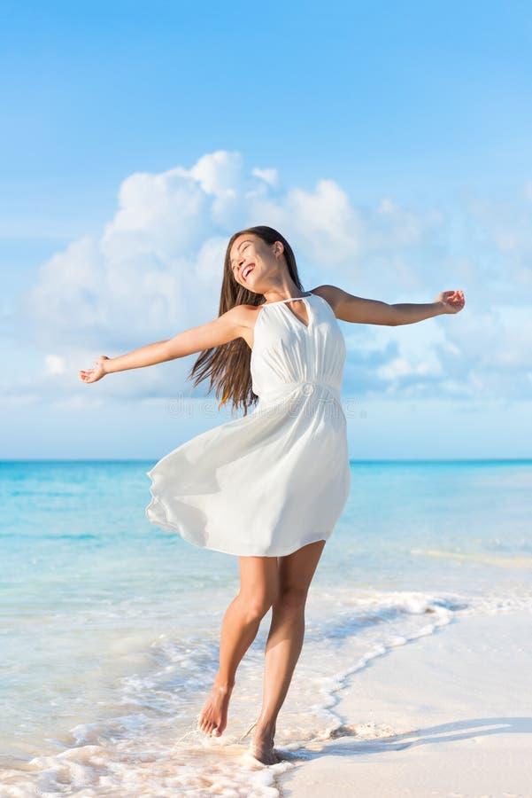 Freiheitsstrandfrau, die freiem Tanzen im Kleid glaubt stockfoto
