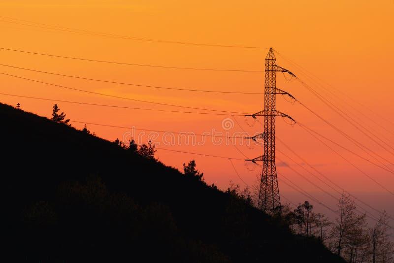 Freileitungsmast bei Sonnenuntergang lizenzfreies stockbild