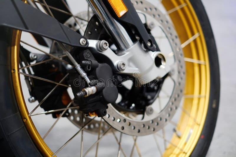 Freio de disco com o cubo de roda no velomotor Feche acima do freio de disco dianteiro na motocicleta Conceitos de cuidados com o fotografia de stock royalty free