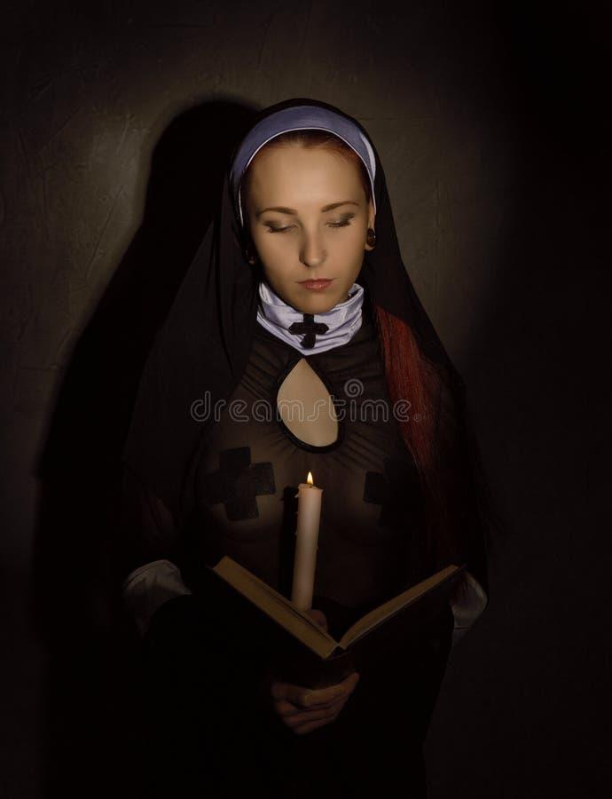 Freira bonita com uma vela que lê a Bíblia Conceito religioso fotografia de stock royalty free