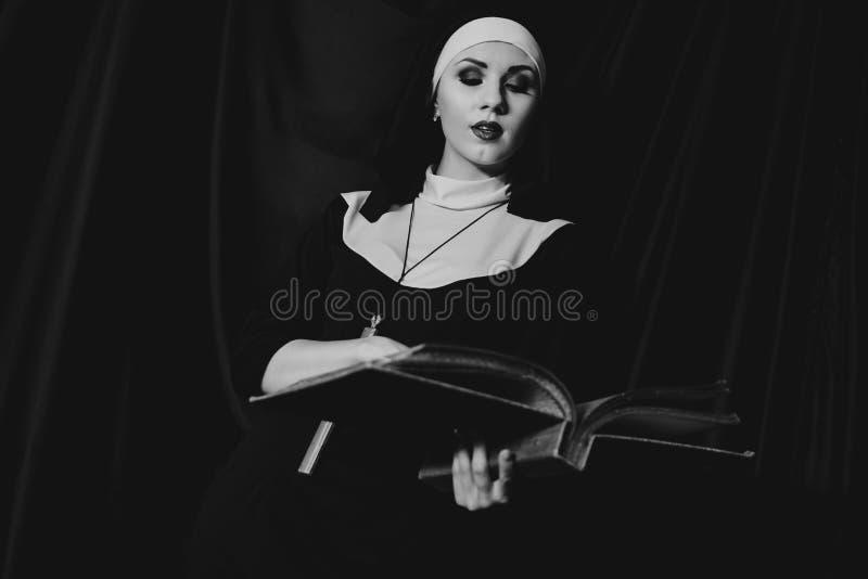 A freira nova bonita no terno do preto da religião guarda a Bíblia Conceito da religi?o imagens de stock royalty free