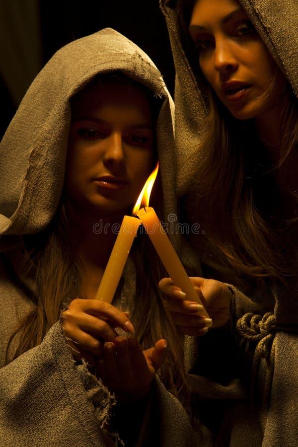Freiras que praing com velas fotografia de stock royalty free