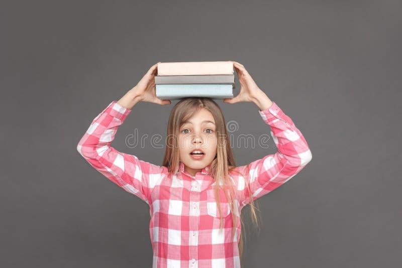 freistil Mädchenstellung lokalisiert auf Grau mit Stapel von Büchern herauf das Schauen der Kamera überrascht stockfoto
